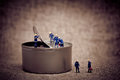 Group of miniature workers opening a can. Color tone tuned macro Royalty Free Stock Photo