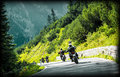 Group of moto bikers on mountainous road highway riding curve pass across alpine mountains extreme lifestyle freedom concept Stock Image