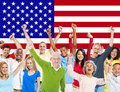 Group of multi ethnic people celebrating expressing positivity with arms raised and american flag as a background Royalty Free Stock Images