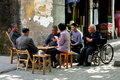 Group older chinese people playing cards seated outside sunny afternoon watched man wheelchair pixian old town sichuan province Royalty Free Stock Photo