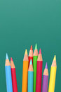 Group of pencils, blackboard behind Royalty Free Stock Photo