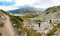 Group people ascending mountain panorama tourist walking trail above lake bulgaria Royalty Free Stock Photo
