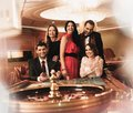 Group of people in casino young behind roulette table a Stock Photo