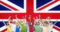 Group of people celebrating united kingdom flag multi ethnic raising their arms and expressing positivity with british as a Stock Photo