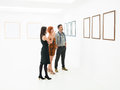 Group of people contemplating artworks stading in a room looking and pointing at the empty frames displayed on white walls Royalty Free Stock Photos