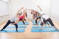 Group of people doing aerobics large diverse exercises in a gym standing on blue mats Stock Photo