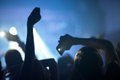 Group of people enjoying a concert silhouettes with raised hands holding phones with flashlights at nightclub Stock Photos