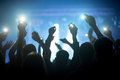 Group of people enjoying a concert silhouettes with raised hands holding phones with flashlights at nightclub Royalty Free Stock Photos