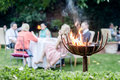 Group of people enjoying a garden party in the foreground firebowl Stock Image