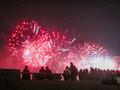 Group of people enjoying spectacular red fireworks show in a carnival or holiday Royalty Free Stock Photo