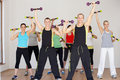 Group of people exercising in dance studio with weights facing camera Royalty Free Stock Image