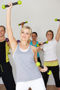 Group of people exercising in dance studio with weights facing camera Royalty Free Stock Images