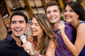 Group of people karaoke signing singing at a bar having fun Stock Images