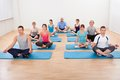 Group of people practicing yoga meditating diverse in a gym sitting cross legged on their mats Stock Photos