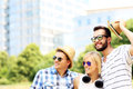 Group of people standing in front of modern buildings a picture a friends looking at something the park Stock Photo