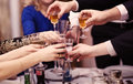 Group of people toasting at a celebration clinking their glasses together in congratulations close up view their hands Stock Photography
