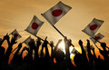 Group of People Waving Japanese Flags in Back Lit Royalty Free Stock Photo