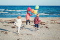 Group portrait of funny white Caucasian children kids with colorful bunch of  balloons, playing running on beach on sunset Royalty Free Stock Photo