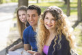 Group portrait with selective focus of students sitting outdoors Royalty Free Stock Photography