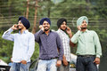 Group portrait smiling authentic native indian punjabi sikh men turban speaking mobile phone Stock Photo