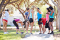 Group of runners warming up before run streaching and Royalty Free Stock Photos