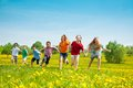 Group of running kids seven in the park boys and girls black and caucasian Stock Image