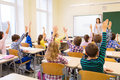 Group of school kids raising hands in classroom Royalty Free Stock Photo