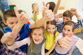 Group of school kids showing thumbs up education elementary learning gesture and people concept and in classroom Stock Photography