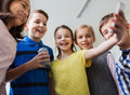 Group of school kids with smartphone and soda can Royalty Free Stock Photo