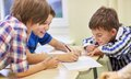 Group of schoolboys writing or drawing at school Royalty Free Stock Photo