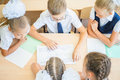 Group of schoolchildren at school classroom sitting at desk Royalty Free Stock Photo