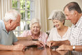 Group Of Senior Couples Enjoying Game Of Dominoes At Home Royalty Free Stock Photo