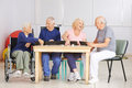 Group of senior people playing rummy game happy in a nursing home Stock Image