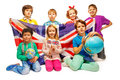 Group of seven kids studying geography with globes happy and holding flag great britain isolated on white Stock Photo