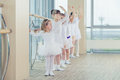 Group of seven little ballerinas standing in row and practicing ballet using stick on the wall Royalty Free Stock Photo