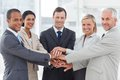 Group of smiling business people piling up their hands together in the workplace Royalty Free Stock Photos