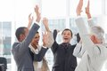 Group of smiling business people raising their hands in the workplace Stock Photography