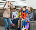 Group of smiling children playing charades sitting on bench and together Stock Photo