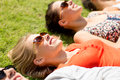 Group of smiling friends lying on grass outdoors friendship leisure summer and people concept Stock Images