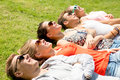 Group of smiling friends lying on grass outdoors friendship leisure summer and people concept Royalty Free Stock Photography
