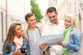 Group of smiling friends with map and photocamera travel vacation technology friendship concept exploring city Royalty Free Stock Photo