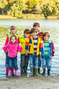 Group of smiling friends in rubber boots and colorful clothing Royalty Free Stock Photo