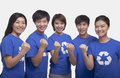 Group of smiling and happy people wearing recycling symbol t shirts standing in a row with raised fists studio shot Royalty Free Stock Photography