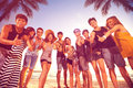 Group of smiling men and women showing thumbs up on beach Royalty Free Stock Photo