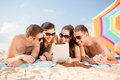 Group of smiling people with tablet pc on beach summer holidays vacation technology and happy concept in sunglasses the Stock Photos