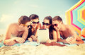 Group of smiling people with tablet pc on beach Royalty Free Stock Photo