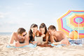 Group of smiling people with tablet pc on beach summer holidays vacation technology and happy concept under umbrella the Stock Images