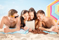 Group of smiling people with tablet pc on beach summer holidays vacation technology and happy concept under umbrella the Royalty Free Stock Images