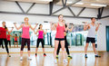 Group of smiling people working out with barbells fitness sport training gym and lifestyle concept in the gym Royalty Free Stock Images