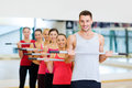 Group of smiling people working out with barbells fitness sport training gym and lifestyle concept in the gym Stock Photos